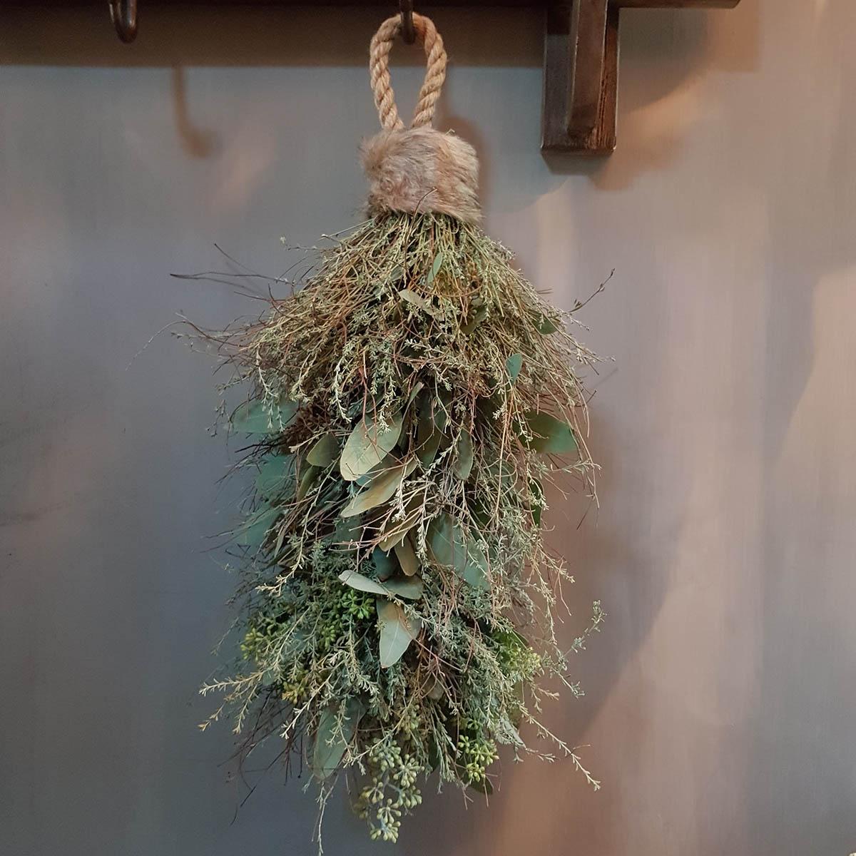 Foto van toef met mos, wilde thijm en eucalyptus hangend aan kapstok voor webshop anterieur authentique.