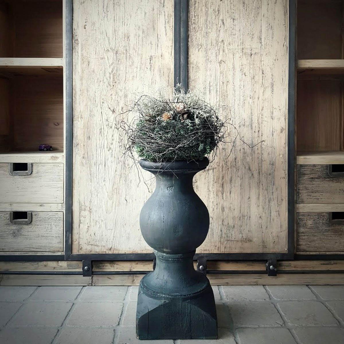 Afbeelding van baluster antraciet olijfgroen met op achtergrond kast voor galerij Antérieur Authentique webshop