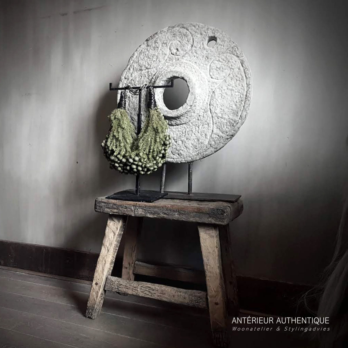 Afbeelding van een molensteen ornament op statief voorzien van groendecoratie geplaatst op Chinees bankje voor gebruik in de webshop van Antérieur Authentique