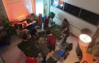 Lich, gezelligheid en groen komen samen tijdens een workshop groendecoratie door Antérieur Authentique op een donkere winteravond.
